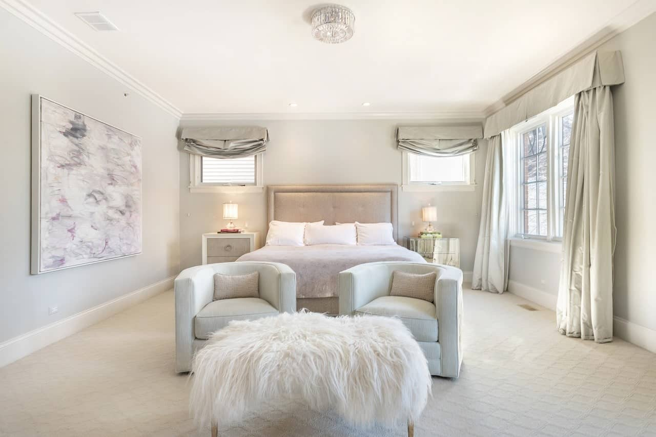 The light palette of this primary bedroom is gorgeous with its white patterned carpeted floors matched with a white ceiling and light gray walls that makes the beige cushioned headboard of the traditional bed stand out.