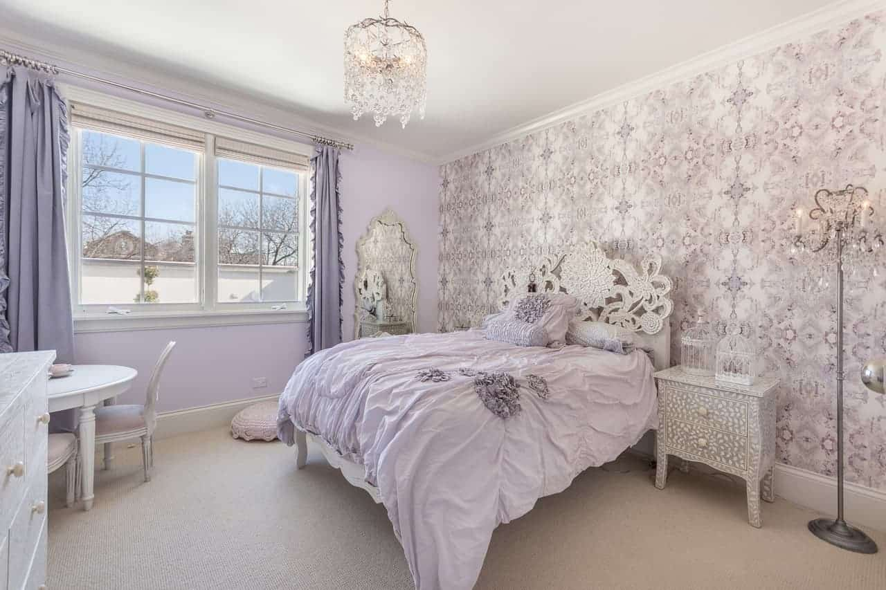 This chic bedroom is fit for royalty with its elegantly patterned light purple walls that match with the intricate patterns of the headboard as well as the crystal chandelier hanging over the purple bed.