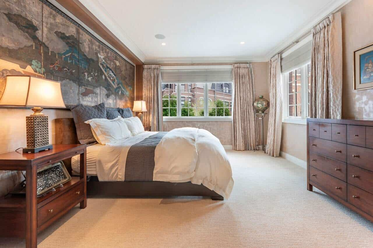 The highlight of this lovely Transitional-Style primary bedroom is the wall art dominating the wall behind the headboard of the traditional bed that has a white and gray palette that complements the beige carpeted flooring and walls.