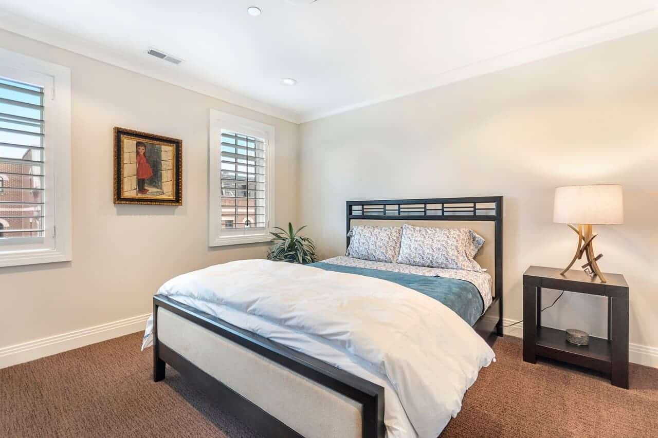 This bedroom has a sleigh bed that has dark wooden frames matching with the bedside table with a table lamp that brightens up the beige walls adorned with a painting mounted by the bed between the windows.