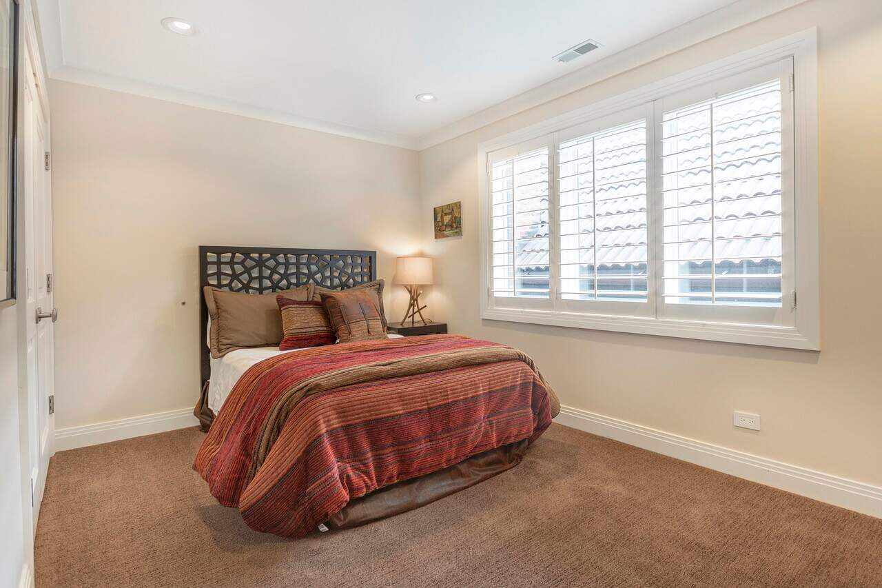 The brown carpeted flooring of this simple bedroom is complemented by the red patterned comforter of the traditional bed that has a dark wooden headboard with patterns that contrast the beige walls and white ceiling.