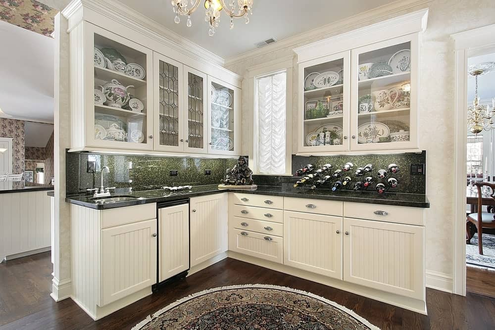 Pantry with transparent glass cabinet doors.