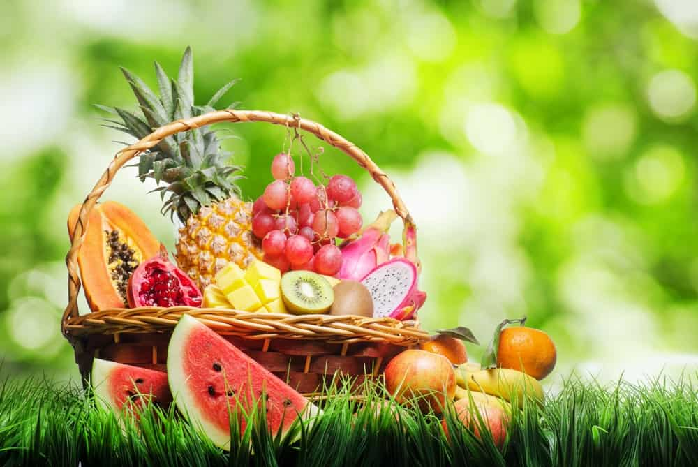 A basket of tropical fruits on green grass.