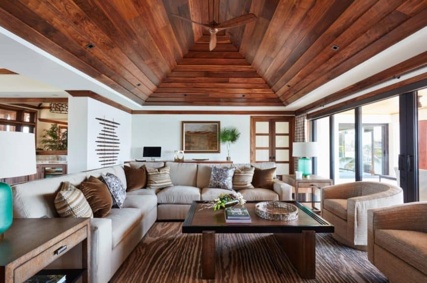 Cozy living room with a cathedral ceiling clad in dark wood plank. It includes an L-shaped sectional paired with round back chairs and wooden coffee table.
