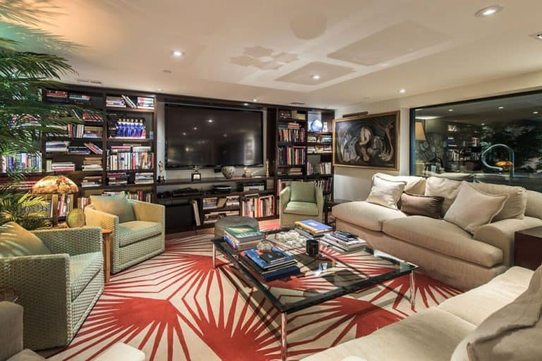 Gorgeous living room features beige sofas and light green armchairs over an eye-catching patterned rug. It has open shelving filled with books and decors.