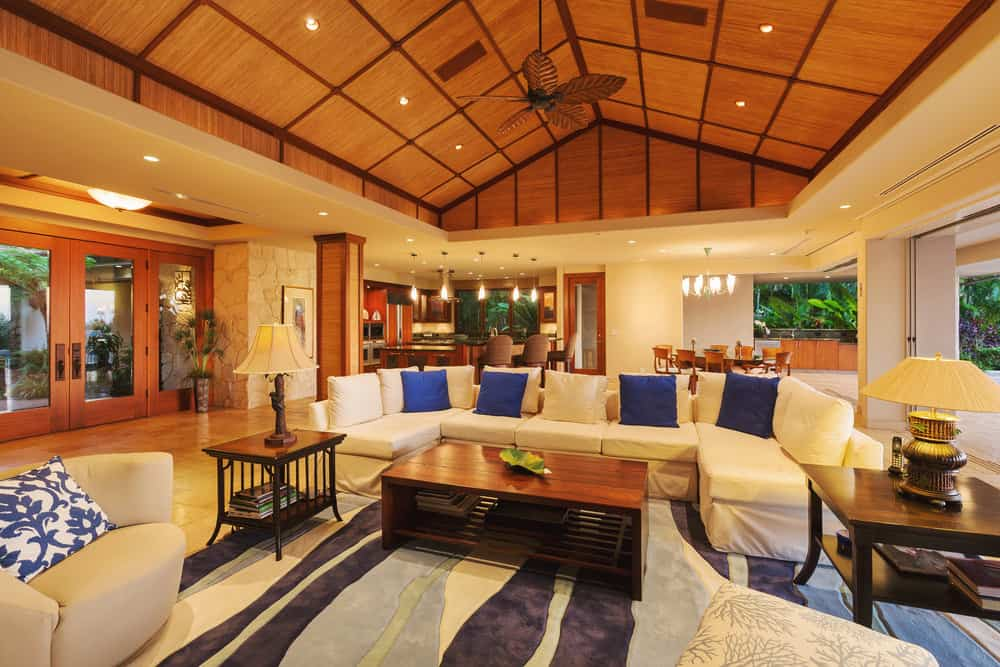 Expansive living room accented with an eye-catching multi-colored rug and blue throw pillows that lay on a white sectional sofa. It has a marble tiled flooring and wood plank cathedral ceiling.