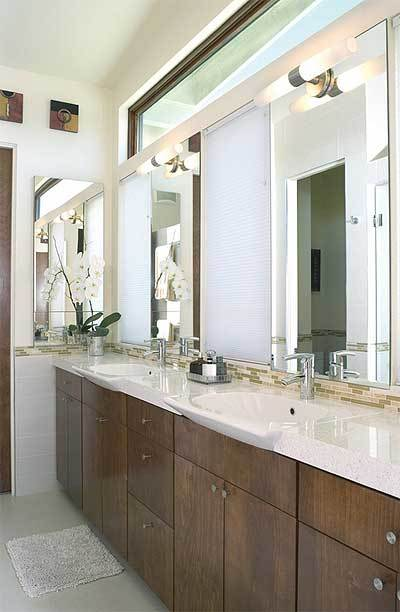 This is a close look at the primary bathroom with dark wooden drawers and cabinets topped with beige counter and wall-mounted mirrors.