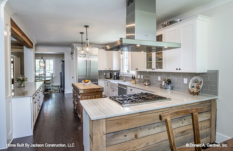 This is a close look at the kitchen that has an L-shaped peninsula paired with a small wooden kitchen island that matches the hardwood flooring.