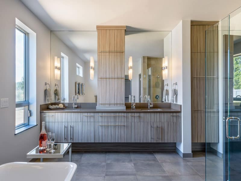 This primary bathroom features a large floating vanity equipped with double sinks, wooden cabinets, and frameless mirrors that span through the ceiling.