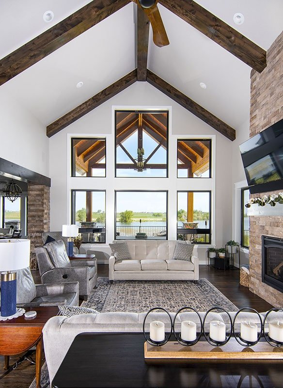 Massive windows and a soaring cathedral ceiling framed with rustic beams help brighten up this craftsman-style living room.