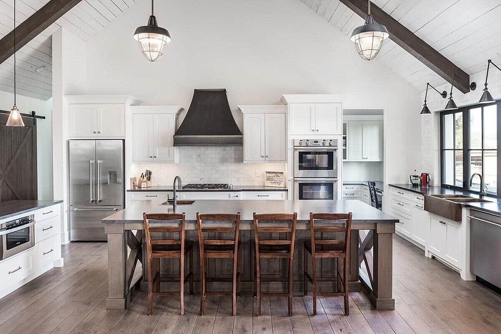 The kitchen has a large kitchen island paired with wooden stools on a hardwood flooring. This is then topped with a white countertop that matches the surrounding cabinetry that makes the stainless steel appliances stand out.