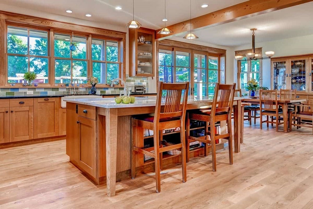This is a close look at the kitche with consistent wooden tones on its kitchen island, stools and cabinetry complemented by the natural lighting that comes from the row of windows.