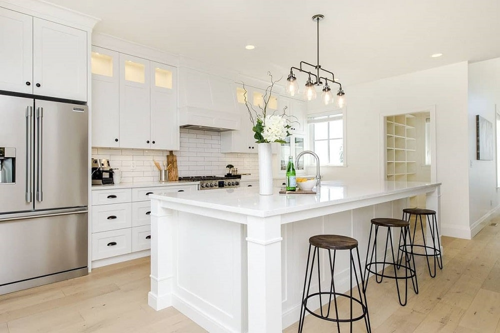 This is a close look at the kitchen that has a large white kitchen island paired with wrought-iron pendant lights that match the stools.