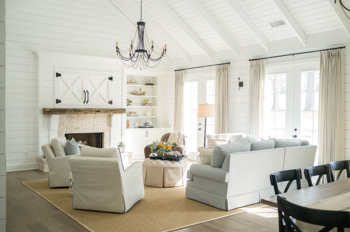 Bright living room with light hardwood flooring, a brick fireplace, and white shiplap walls that extend to the beamed ceiling. French doors dressed in neutral drapes extend the living space outdoors.