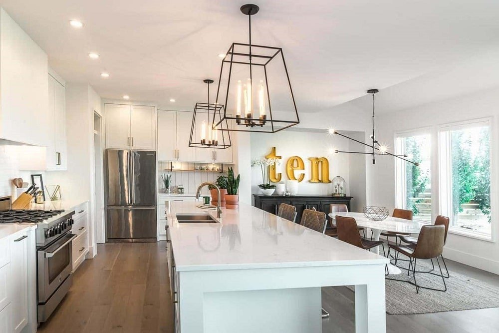 An eat-in kitchen features a marble-top island, white cabinetry, and contemporary pendant lighting.