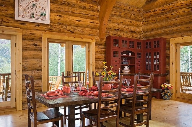 This charming informal dining room has tall log beam walls adorned with a large dark brown cabinet that matches the dark wooden dining set in the middle of the hardwood flooring illuminated by the glass doors.