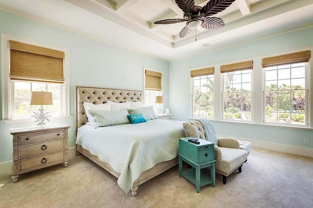 A comfy tufted bed, light wood nightstands and a striped armchair flanked by a green side table and ottoman fill the primary bedroom. These are then complemented by the coffered ceiling and glass windows that bring in natural lights.