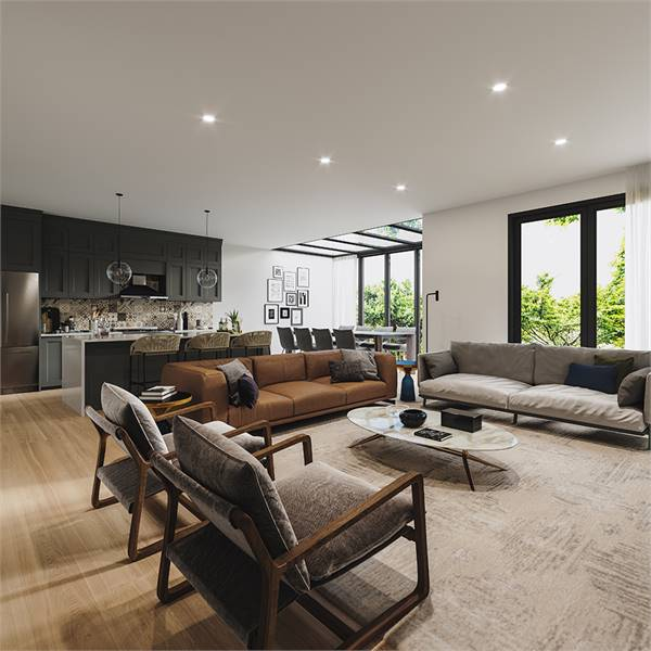 An open living area with an oval dining table and fabric seats in gray and brown hues. A large distressed rug helps define the living space from the kitchen and dining.