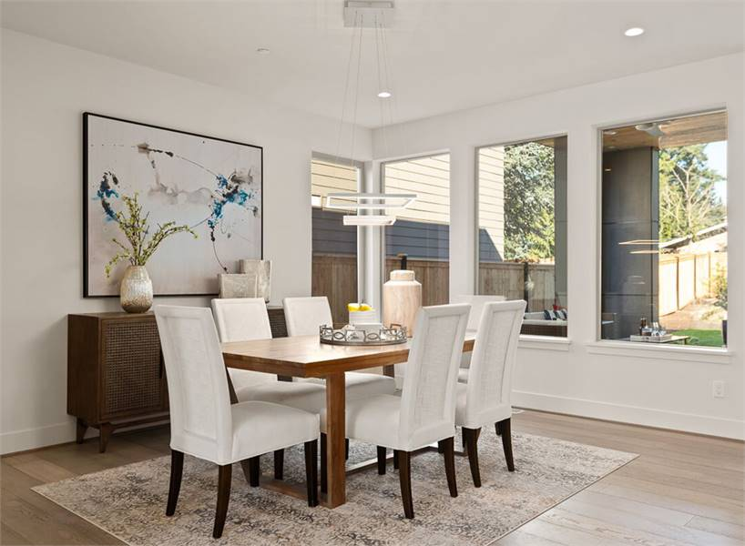 This dining room features a rectangular dining set and a wooden buffet bar adorned with a lovely painting. Sleek glass windows bring in ample natural light.