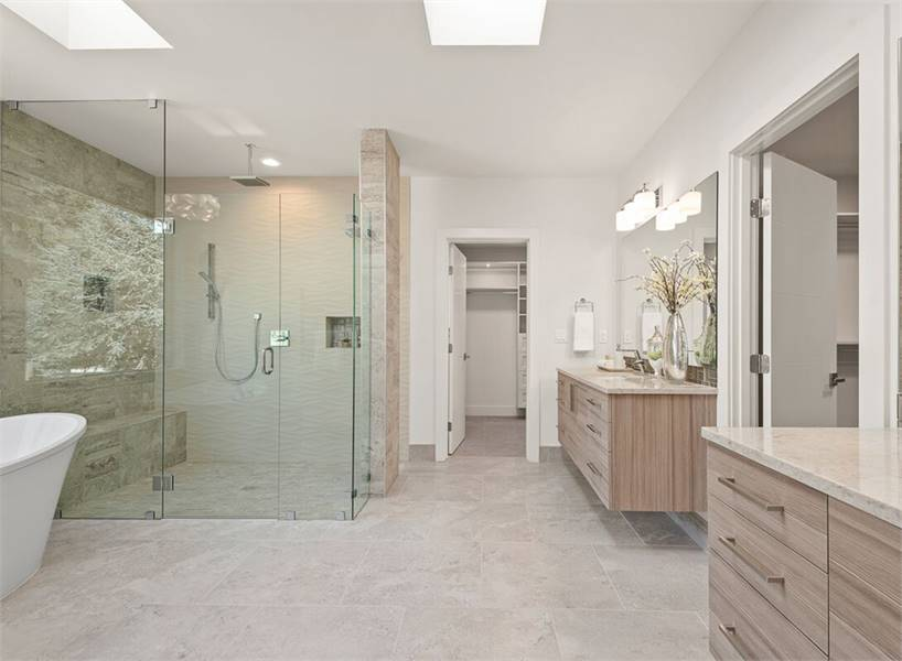 Primary bathroom with a spacious shower area and two floating vanities crowned with beige marble countertops. A couple of skylights enhance the spacious feel as it brings ample natural light.