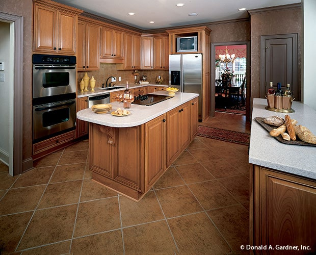 The kitchen has beige flooring tiles to pair with the wooden cabinetry that matches with the kitchen island that has a beige countertop. These elements make the stainless steel appliances stand out.