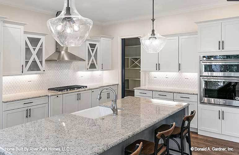 The kitchen is equipped with a double wall oven, a built-in cooktop, white cabinetry, and a breakfast island that is topped with glass pendant lights hanging from a white ceiling.