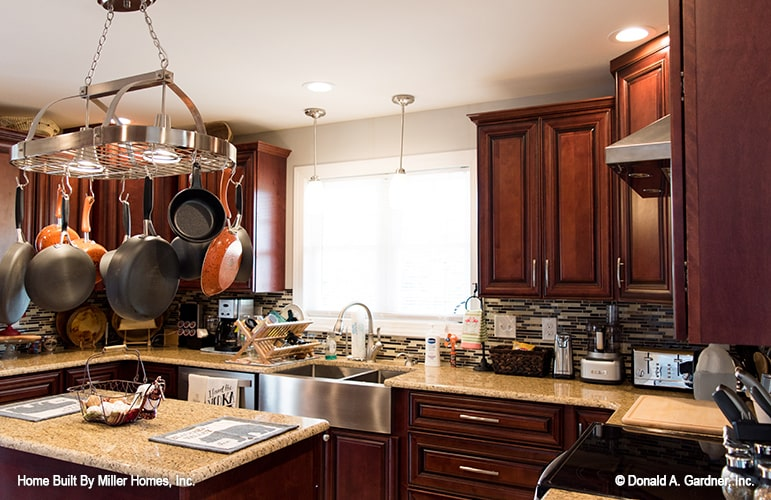 This is a close look at the kitchen that has a small kitchen island topped with a hanging pot rack surrounded by dark wooden cabinetry and beige countertops.