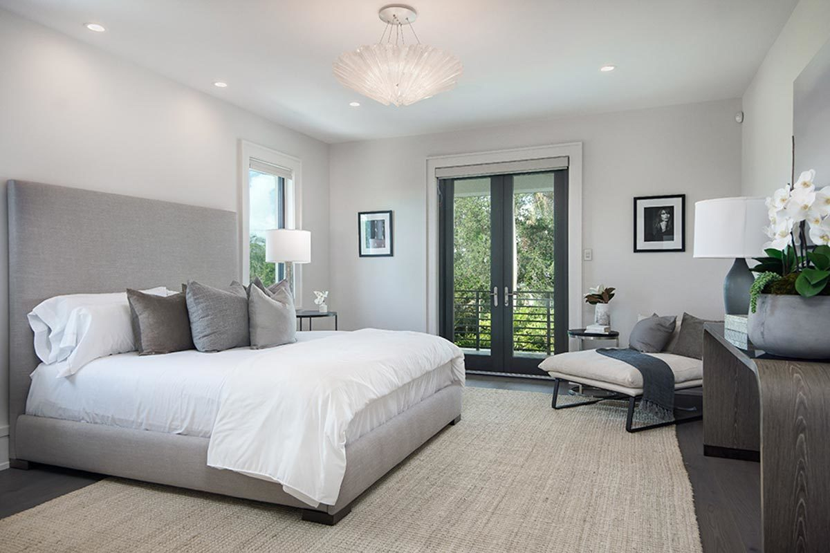 The primary bedroom features pristine white walls, a jute area rug, a sitting area, and a private balcony accessible through the french door.