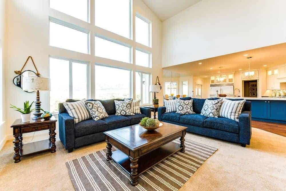 The bright living area features dark wood tables, a striped area rug, and deep blue sectionals that add a pop of color to the room.