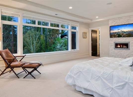 This is a spacious bedroom with a beige carpeted flooring that matches with the walls and ceiling. These are then complemented by the large glass window across from the bed with a comfortable sitting area.