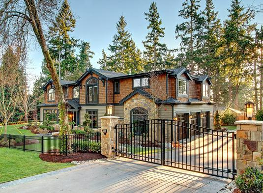 This is the view from the front of the house showcasing the wrought iron main gate that matches with the wrought iron fencing supported by stone pillars that bear outdoor lamps. The earthy tones of the house is complemented by the lush green lawn and tall trees in the background.