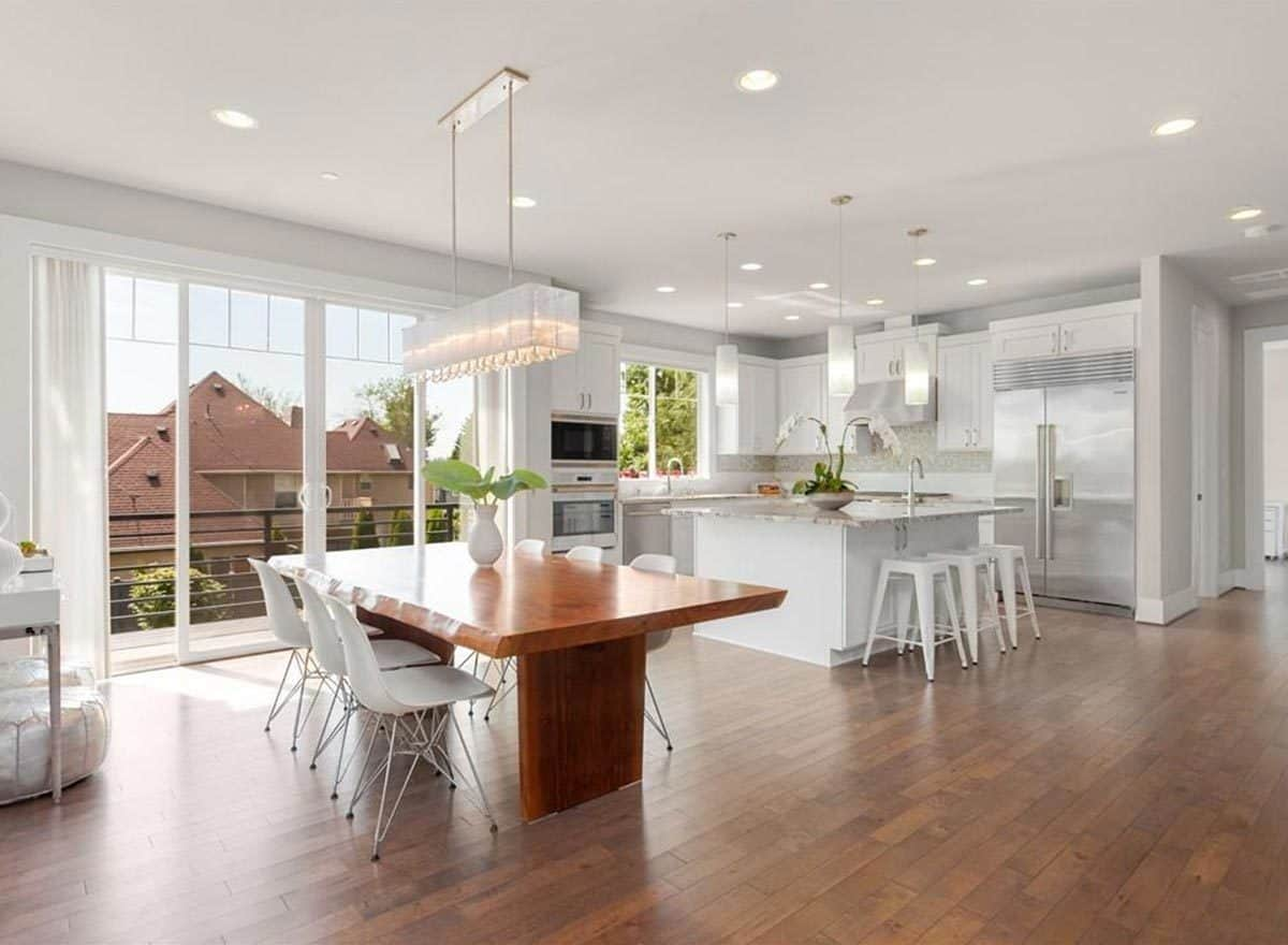 An open dining area with white modern chairs and a large wooden dining table topped with a linear chandelier. It flows right into the kitchen brightened by recessed ceiling lights and cylindrical pendants.