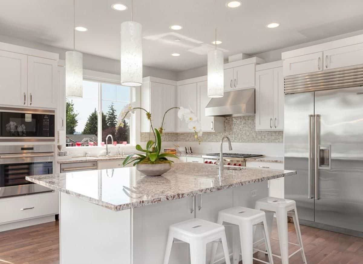 White kitchen brightened by recessed ceiling lights, cylindrical pendants, and natural light streaming in through the windows above the sink.