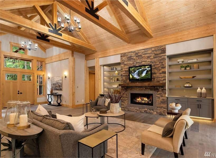 Natural wood elements running throughout the living room creates a warm and cozy atmosphere while a stone fireplace sets a dramatic focal point.