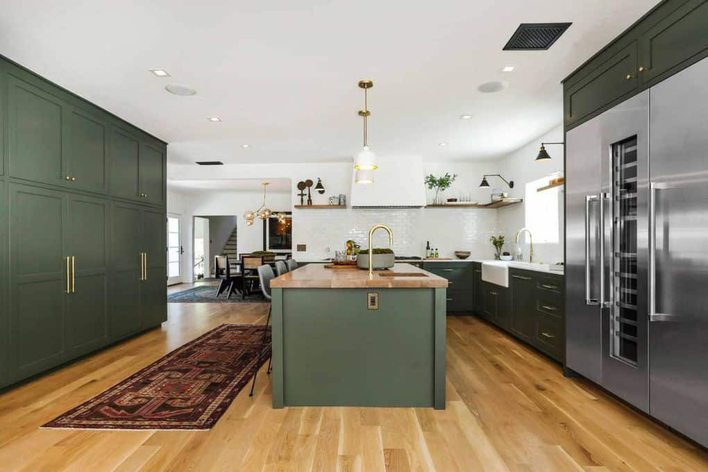 The white ceiling and hardwood flooring of this spacious kitchen is complemented by the green shaker cabinets and drawers of the L-shaped peninsula and the kitchen island topped with golden pendant lights that match the golden faucet.