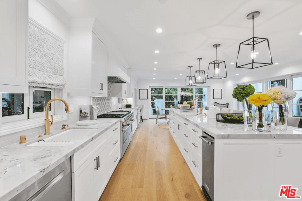 This kitchen saves space by having a long white kitchen island that runs parallel with the kitchen peninsula creating a narrow spot of light hardwood flooring as a work area for the kitchen. This is brightened by the recessed lights of the white ceiling.