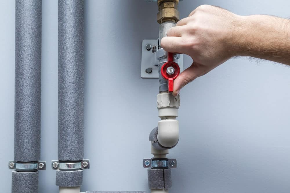 Turning on or off a water supply in a boiler room.