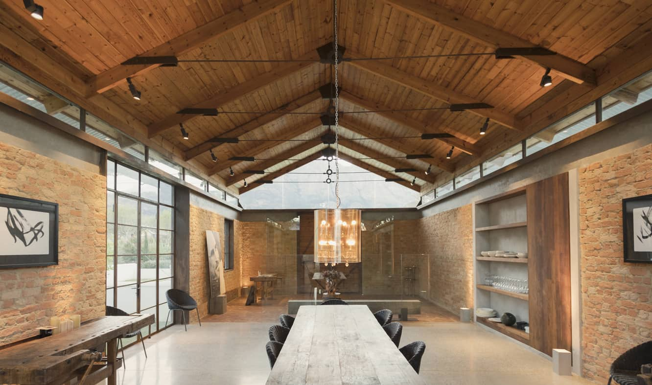 Spacious dining room offers a wooden table surrounded with gray dining chairs over concrete flooring. It has brick walls and a wood cathedral ceiling with track lighting.