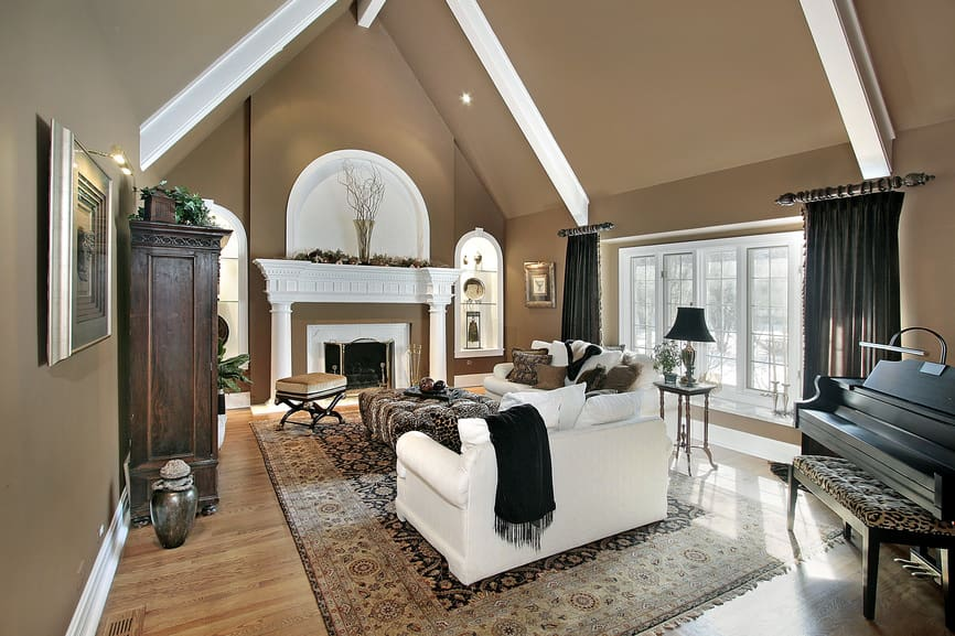 Brown living room with crown molding and white beams attached to the cathedral ceiling. It includes white sofas that sit on a vintage rug facing the fireplace framed with white mantel.