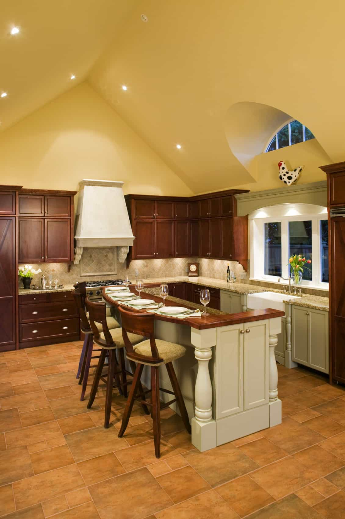 Wooden chairs sit on a two-tier kitchen island topped with rich wood and marble counters in this farmhouse kitchen. It has yellow walls and cathedral ceiling along with tiled flooring.