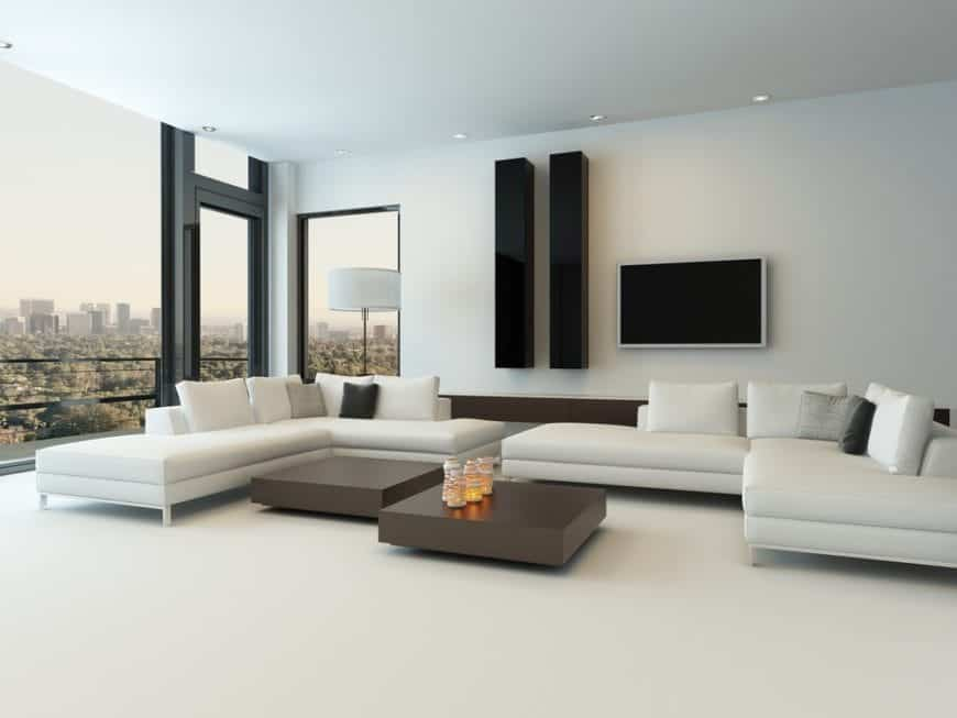 Sleek living room showcases a pair of L-shaped sofas and dark wood coffee tables over white flooring. It has a television mounted next to the minimalistic wall decors.