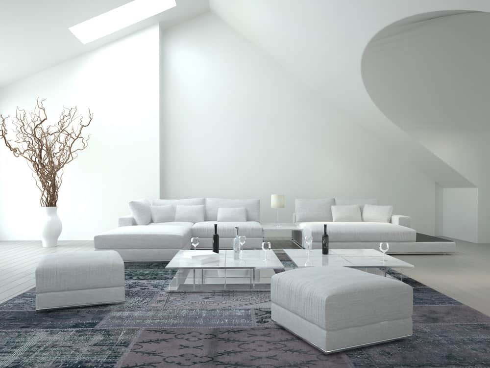 Minimalist living room decorated with a twig tree on a white vase over white wood plank flooring topped with a printed area rug.