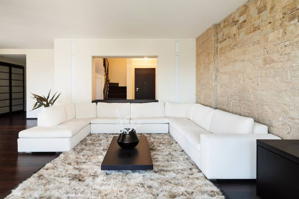 Magnificent living room features a white U-shaped sectional and black coffee table on a shaggy rug. It has dark wood plank flooring and a stone brick accent wall.