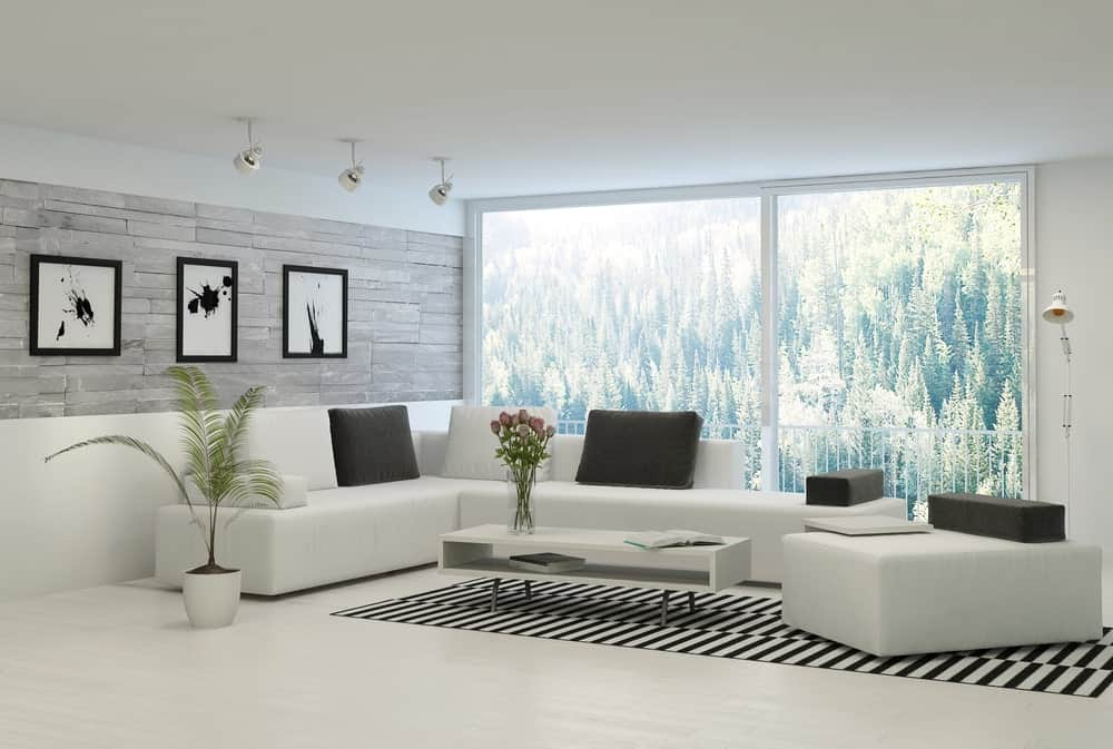 Black and white living room showcases abstract wall art pieces mounted on the gray brick wall. It includes a floor to ceiling windows with an amazing greenery view.