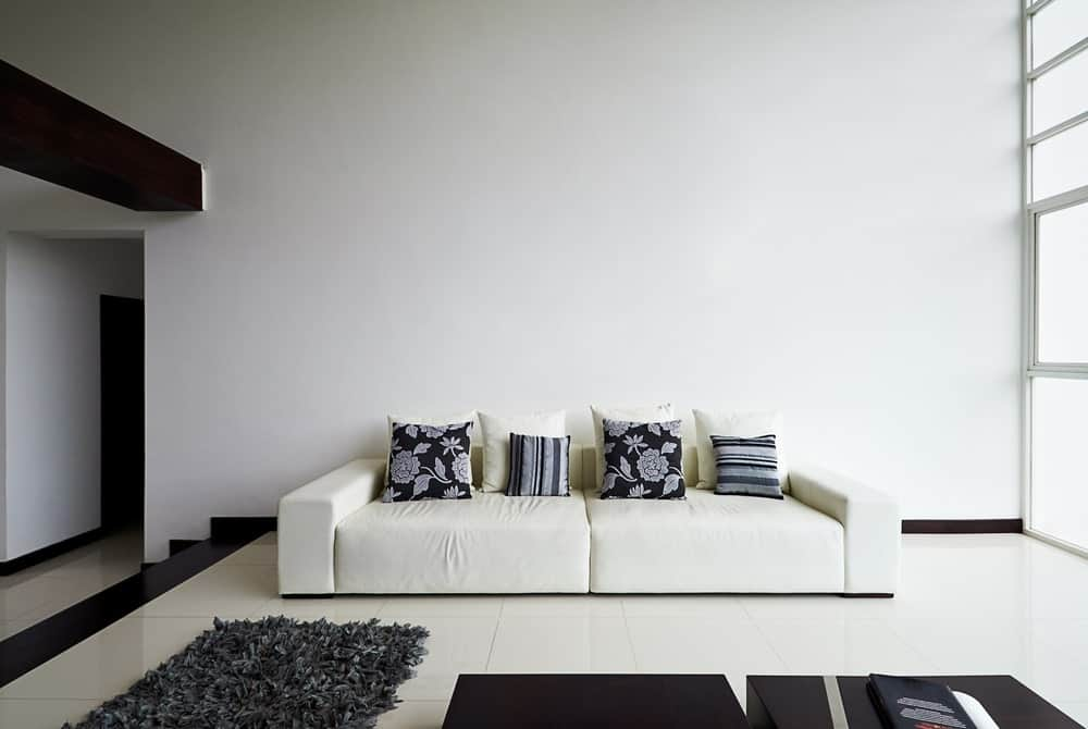 This living room offers a white couch accented with black floral and striped pillows. It is accompanied by a pair of wooden coffee tables and a gray shaggy rug.
