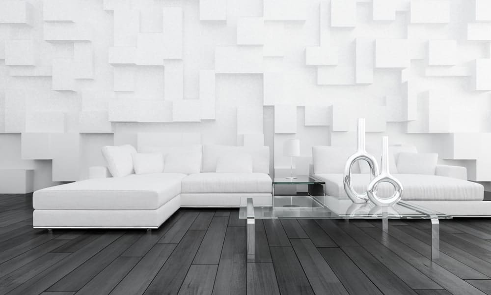 Minimalist living room boasts a 3d wall panel and black wood plank flooring. It includes white sofas and a glass center table topped with contemporary decors.