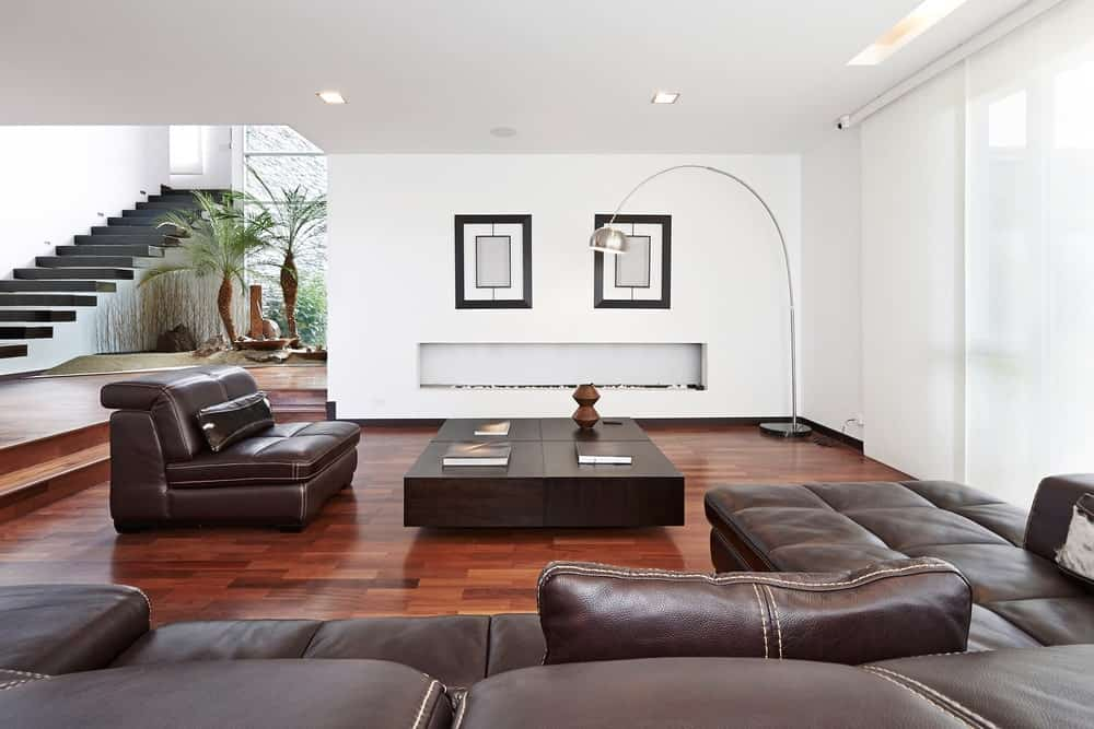 A huge leather sofa faces its matching couch and a modular coffee table lighted by an arched floor lamp in this white living room.