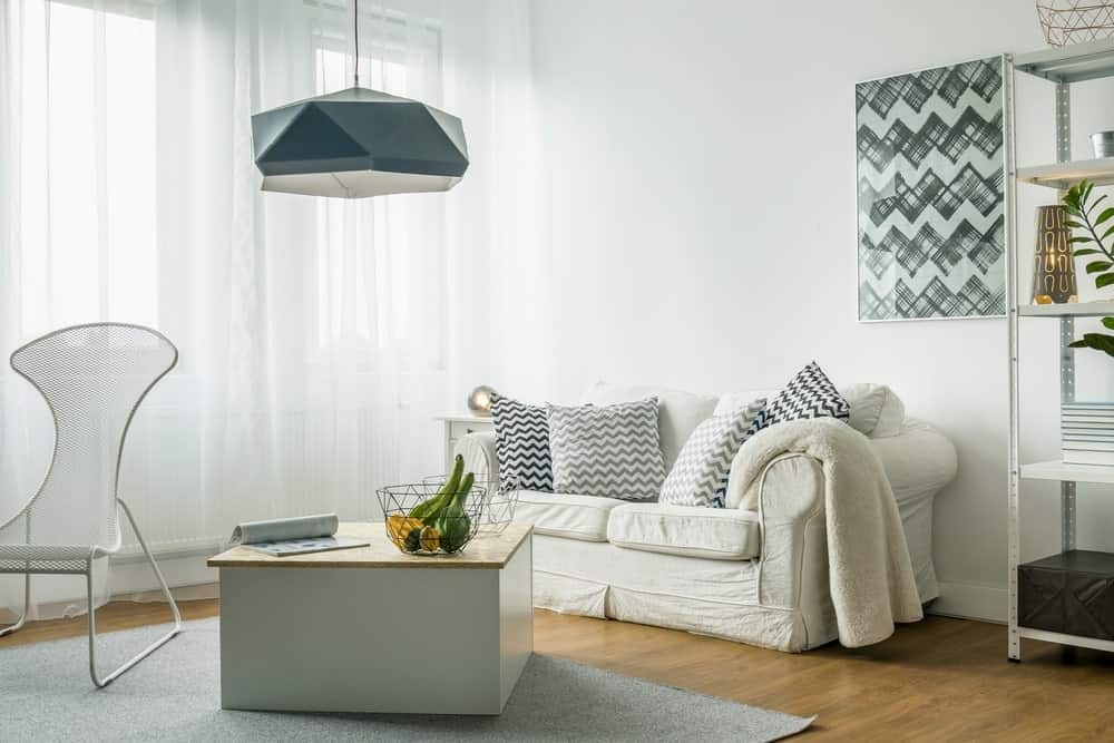 An airy living room illuminated by a geometric chandelier that hung above a wooden coffee table. It is accompanied by a white skirted sofa and a perforated chair that sits on a gray rug.