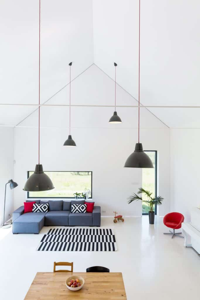 White living room boasts a high cathedral ceiling with hanging black pendants. It has a grayish blue sofa accented with red and black patterned pillows along with a striped rug.