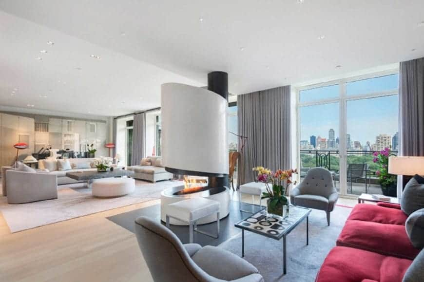 Formal living room features two sitting areas with a modern double sided firework in the middle. It has glass doors covered with gray draperies leading to the balcony.